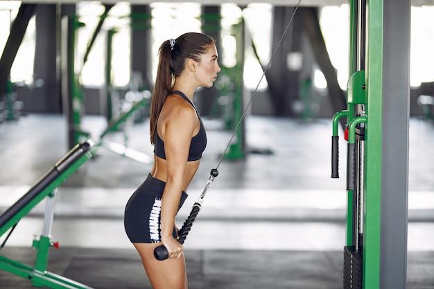 Bawi się brunetki kobiety w sportowym szkoleniu w gym