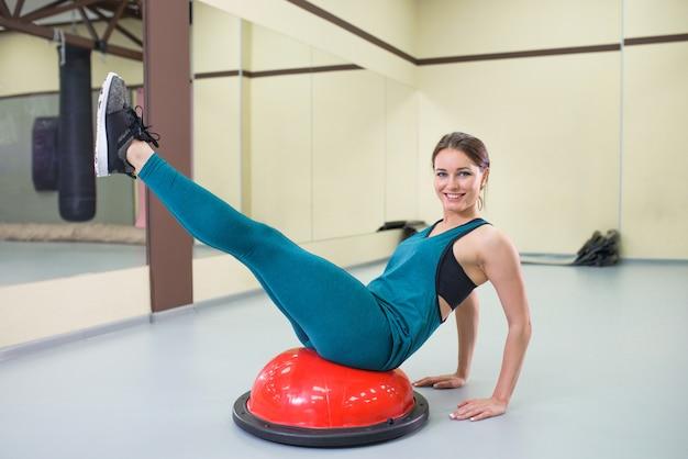 Bawi się kobiety ćwiczenie z pilates piłką przy gym, uśmiechnięty i patrzejący kamerę