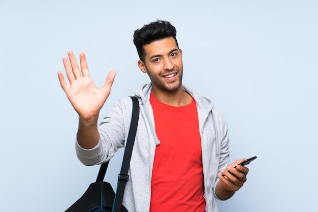 Bawi się mężczyzna nad odosobnioną błękit ścianą salutuje z ręką z szczęśliwym wyrażeniem