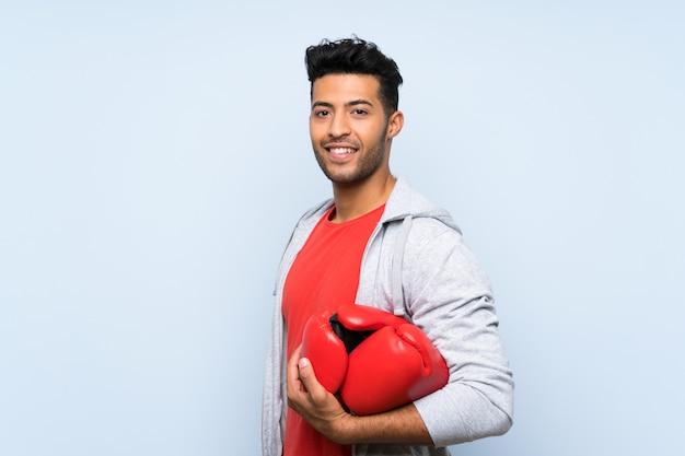 Bawi się mężczyzna z bokserskimi rękawiczkami nad odosobnioną błękit ścianą