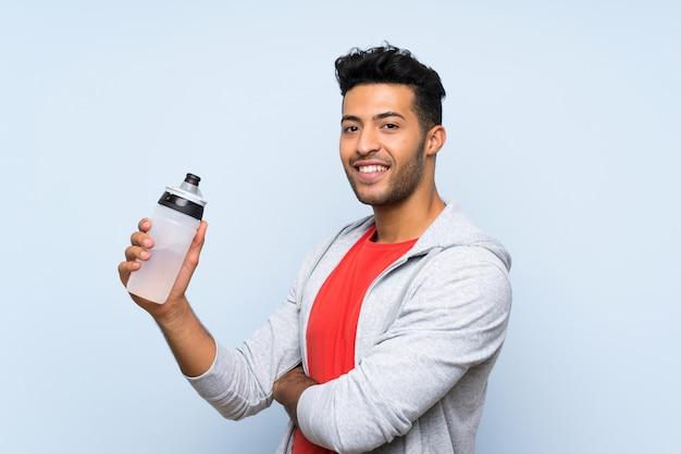 Bawi się mężczyzna z butelką woda nad odosobnioną błękit ścianą