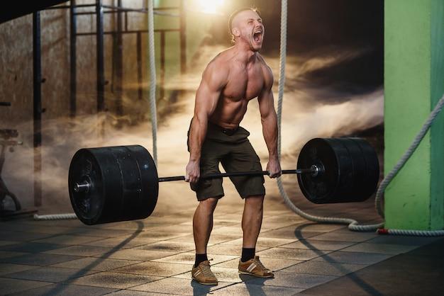 Bawi się młodego człowieka robi kucaniu z barbell w gym.