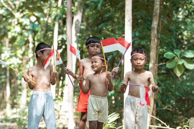 Bawiąca się grupa dzieciaków stojących bez ubrania, trzymając małą biało-czerwoną flagę i podnosząc flagę