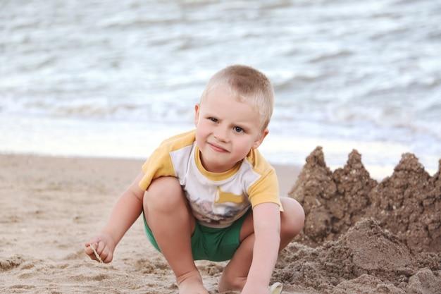 Bawiące się dziecko z zabawnym wyrazem twarzy. wybrzeże morza. reszta rodziny.