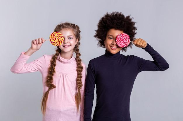 Bawić się cukierkami. uśmiechnięte, rozpromienione dzieciaki w golfach podczas robienia zdjęć i trzymania kolorowych cukierków przed twarzami