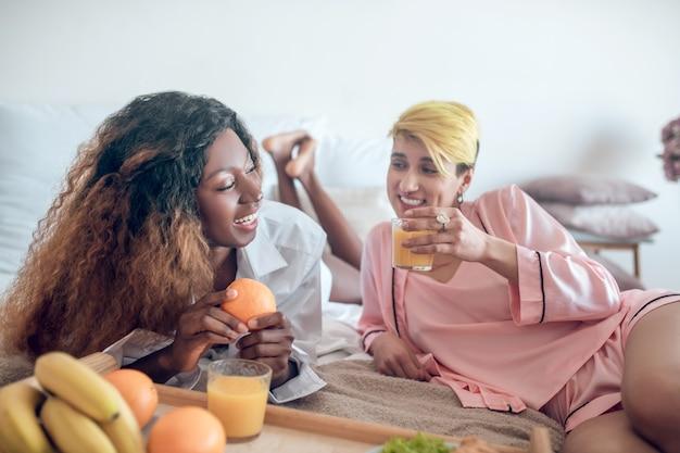 Bawić się. dwie młode ładne dziewczyny w bieliźnie, śmiejąc się, mając śniadanie, leżąc na łóżku w sypialni