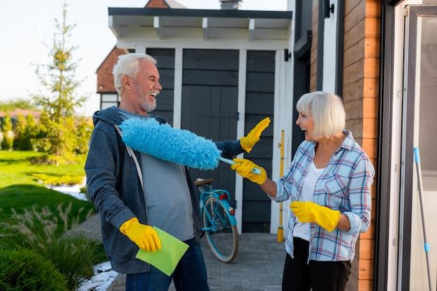 Bawić się. śmiejąca się starsza para przystojny, zabawy podczas sprzątania w pobliżu letniego domu