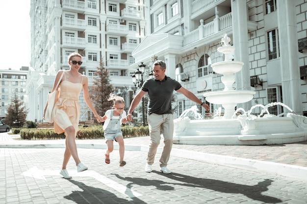 Bawić się. szczęśliwa rodzina nuklearna trzymająca się za ręce przeskakująca razem wzdłuż ulicy z piękną architekturą.
