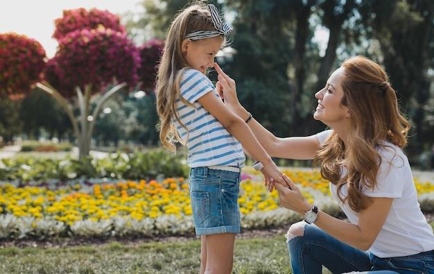 Bawić się. wesoła modna mama dobrze się czuje podczas zabawy z uroczą dziewczyną w parku