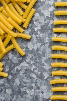 Bawić się z surowym makaronu makaronem na kruszcowym tle