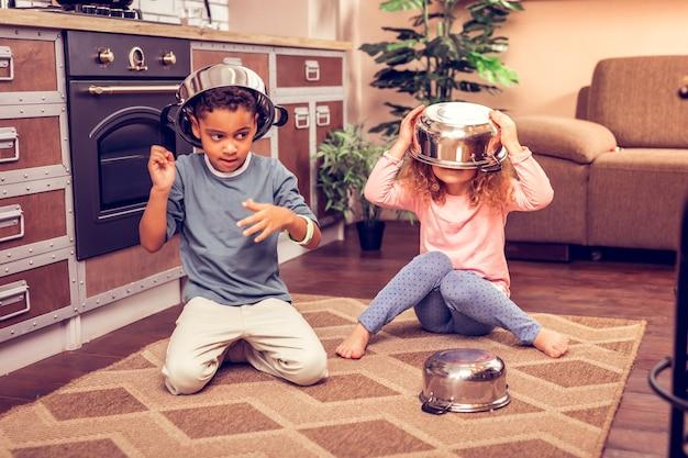 Bawić się. zabawna dziewczyna siedzi obok kuzyna i wkłada patelnię na głowę