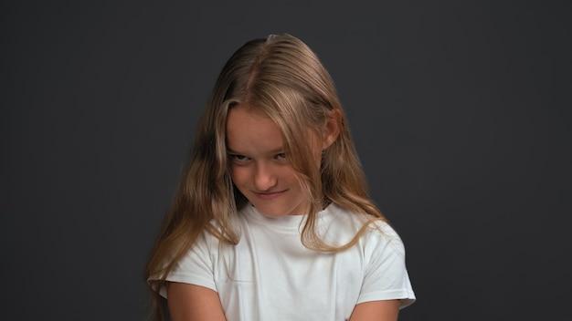 Bawiła się zdenerwowana lub pokonana mała dziewczynka słuchająca rodziców z założonymi rękami, radośnie patrząc na przód w białej koszulce i czarnych spodniach odizolowanych na czarnej ścianie