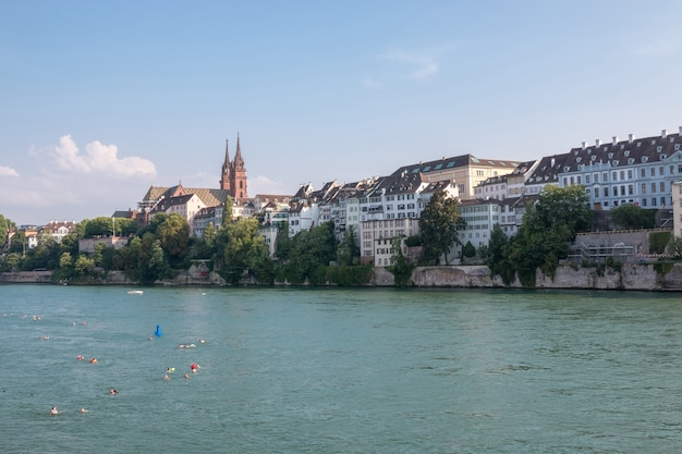 Bazylea, szwajcaria - 23 czerwca 2017 r.: widok na miasto bazylea i ren. letni krajobraz, słoneczna pogoda, błękitne niebo i słoneczny dzień. ludzie pływają w rzece