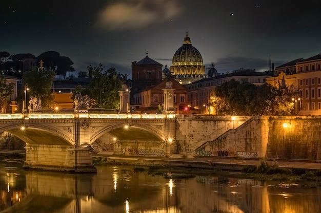 Bazylika św. piotra w watykanie widoczna z mostu elijewa i tybru nocne zdjęcie na tle rozgwieżdżonego nieba rzym włochy