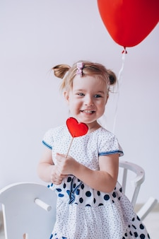 Bblonde dziewczyna je karmel lollypop w kształcie serca. dziecko siedzi na białym drewnianym koniu z czerwonymi balonami w kształcie serca.