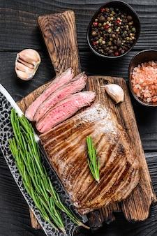 Bbq grillowany stek wołowy z boku lub klapy na drewnianej desce do krojenia. czarne drewniane tło. widok z góry.