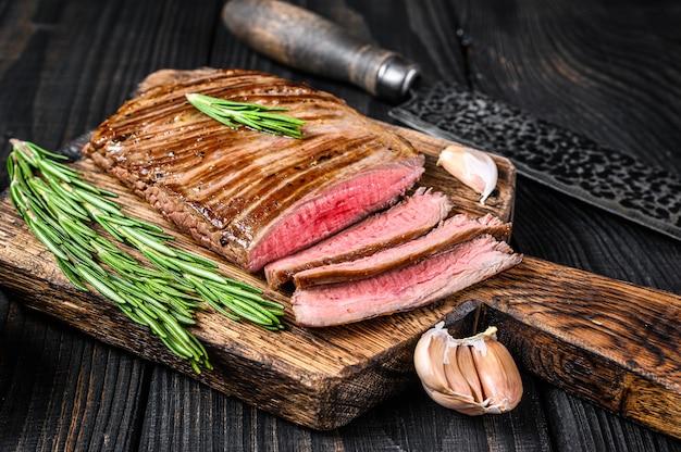 Bbq grillowany stek z mięsa wołowego z boku lub z klapą na drewnianej desce do krojenia. czarne drewniane tło. widok z góry.