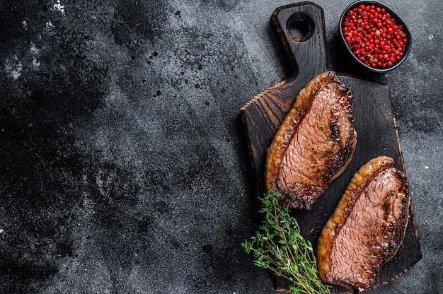 Bbq grillowany top polędwicy lub stek picanha na drewnianej desce do krojenia na drewnianym stole. widok z góry.