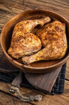 Bbq udka z kurczaka z grilla w drewnianym talerzu z ziołami