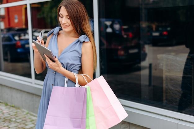 Bbusinesswoman z kolorowymi torba na zakupy zbliża centrum handlowe