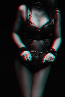 Bdsm. dziewczyna w kajdankach i seksowną czarną skórzaną bieliznę.