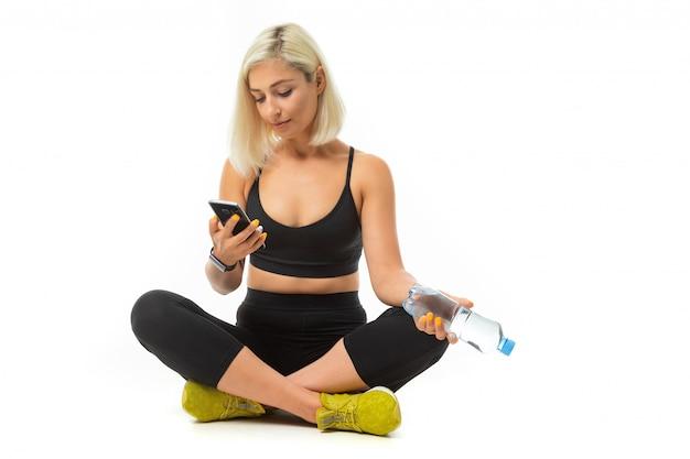 Beauiful sportowa kaukaska dziewczyna siedzi na podłodze, krzyżuje nogi, trzyma telefon komórkowy i butelkę wody, rozmawia z przyjaciółmi lub rodziną na białym tle