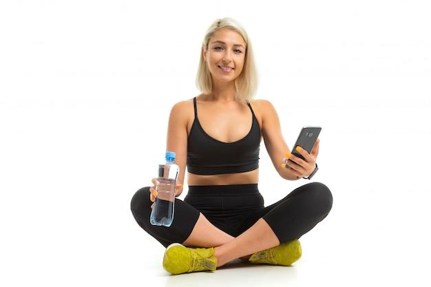 Beauiful sportowa kaukaska dziewczyna siedzi na podłodze, krzyżuje nogi, trzyma telefon komórkowy i butelkę wody, rozmawia z przyjaciółmi na białym tle