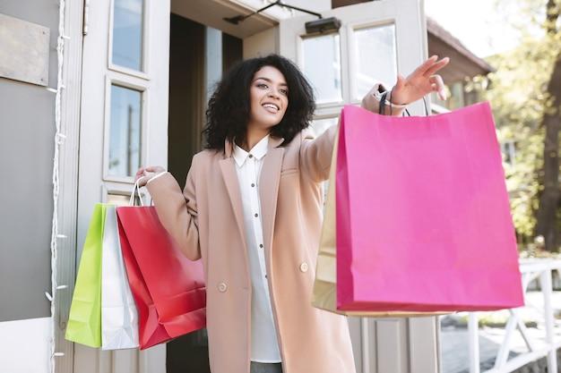 Beautiful african american girl z ciemnymi kręconymi włosami stojąc z torby na zakupy w dłoniach. młoda uśmiechnięta dama łapie taksówkę z pakietami