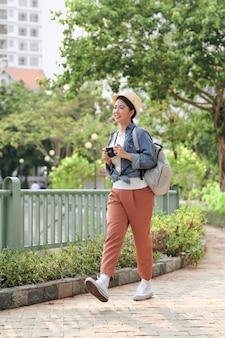 Beautiful asian kobieta backpacker trzymając aparat podróż na ulicy. młoda dziewczyna uśmiechając się plecak z aparatem.