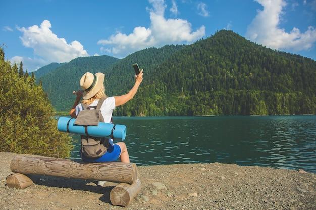 Beautiful girl traveller robi zdjęcia dużego niebieskiego górskiego jeziora w tle gór