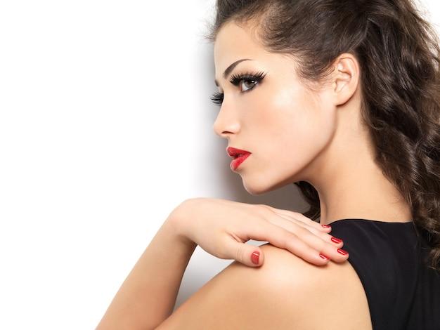 Beautiul modelka z czerwonym manicure i ustami na białym tle