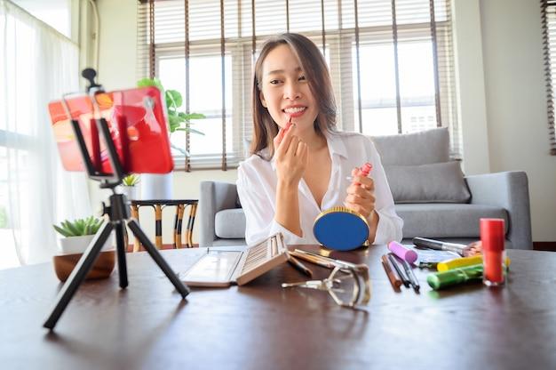 Beauty blogger influencer azjatycka kobieta korzystająca ze smartfona na żywo recenzuje kosmetyki w salonie w domu