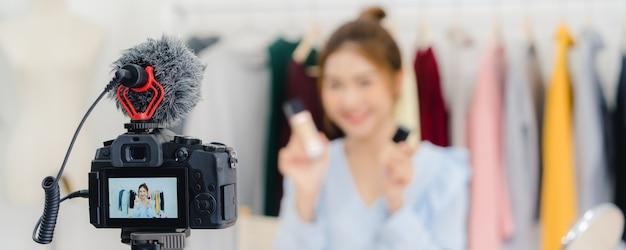 Beauty blogger przedstawia kosmetyki kosmetyczne siedzące nagrywając kamerę wideo