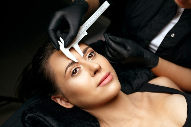 Beauty master mierzący brwi suwmiarką przed makijażem permanentnym w proszku. strzał zbliżeniowy