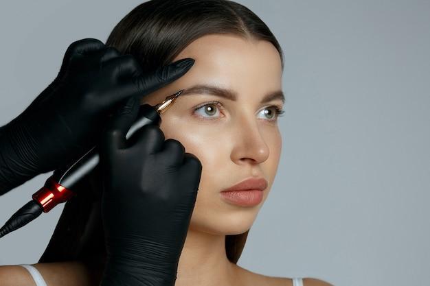 Beauty master stosując makijaż permanentny brwi w gabinecie kosmetycznym. miejsce na tekst. studio strzał na szarym tle
