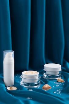 Beauty mineralny krem nawilżający, muszelki, sól morska w szklanym słoiku, niebieska drapowana szmatka.