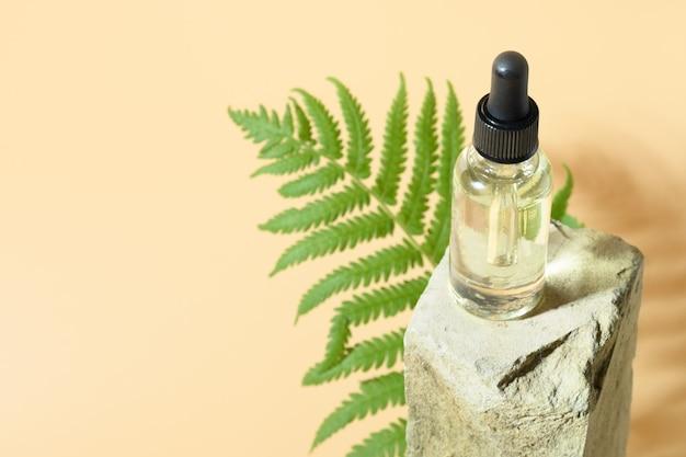 Beauty olej kosmetyczny w szklanej butelce na kamiennym podium na beżowej przestrzeni na projekt lub tekst or