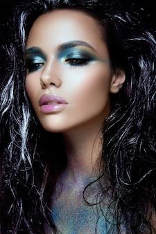 Beautyful dziewczyna z niebieskim brokatem na twarzy