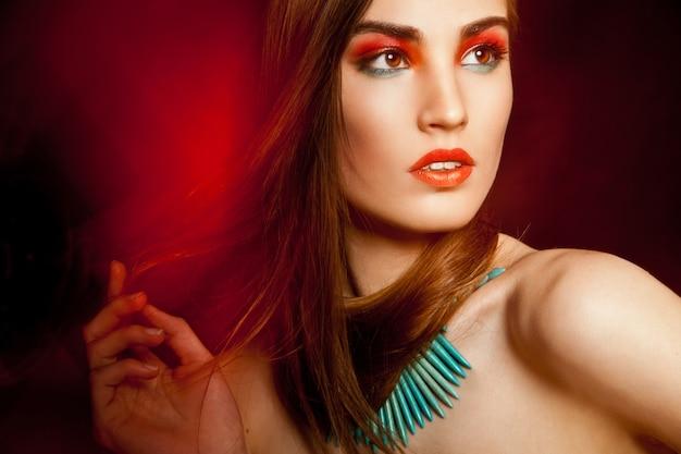 Beautyful kobieta z kreatywnym makijażem na ciemnym tle