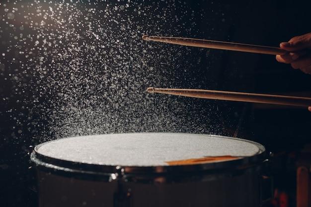 Bębny wbijają rytm bębnów na powierzchnię bębna z rozbryzgami wody
