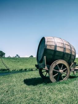 Beczka na wino w polu zielonej trawy w tonie vintage