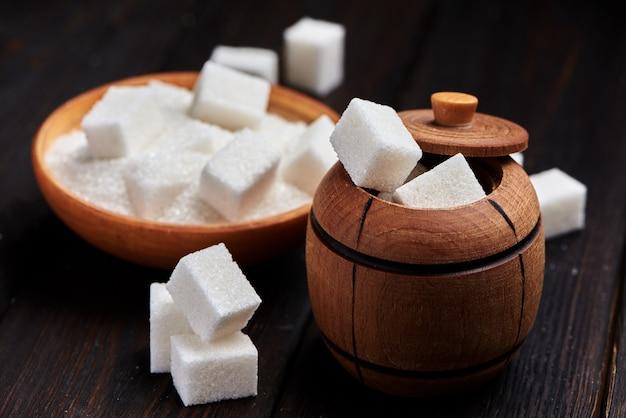 Beczka z białym piaskiem i gęstym cukrem na drewnianym tle