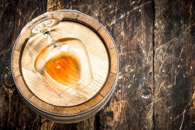 Beczka ze szklanką koniaku. na drewnianym tle.