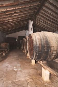 Beczki czerwonego wina ułożone w starej piwnicy winnicy w hiszpanii, alicante