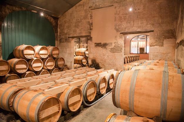 Beczki wina ułożone w starej piwnicy