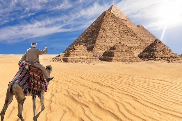 Beduin z pustyni giza przed wielkimi piramidami w egipcie.