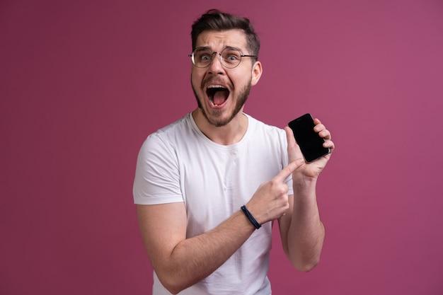 Będziesz miał problemy stary! portret zły zdezorientowany agresywny w złym nastroju facet krzyczący grożąc w głośniku swojego smartfona, na białym tle na różowym tle.