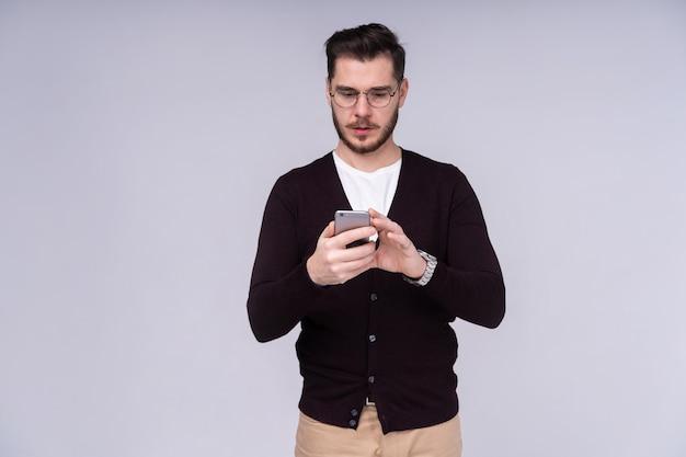 Będziesz miał problemy stary! portret zły zdezorientowany agresywny w złym nastroju facet krzyczący grożąc w głośniku swojego smartfona, na białym tle na szarym tle.