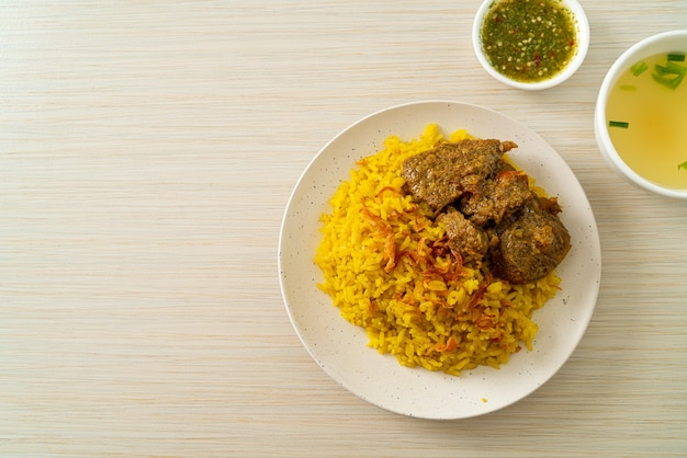 Beef biryani lub curried rice and beef - tajska-muzułmańska wersja indyjskiego biryani, z pachnącym żółtym ryżem i wołowiną - muzułmańska kuchnia