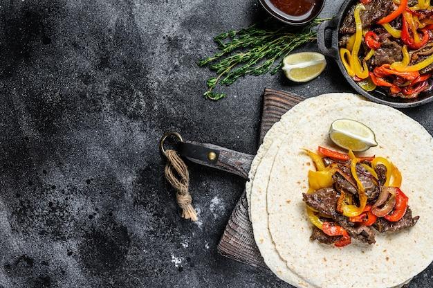 Beef steak fajitas z tortillą, papryką i cebulą tradycyjne meksykańskie jedzenie widok z góry.